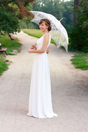 woman with umbrella: Beautiful happy laughing bride in white dress with decorative umbrella against background green nature  In a summer park Stock Photo