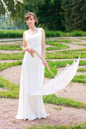 White elegant woman in white dress with decorative umbrella in a vintage style against background green nature photo