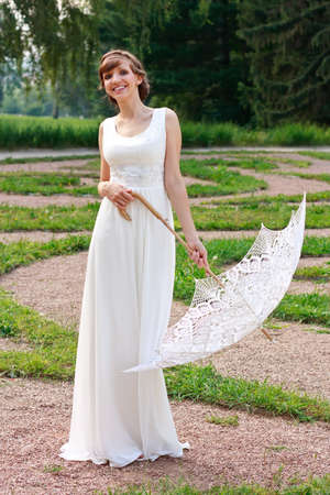 Beautiful happy smiling girl in white dress with decorative umbrella against background green summer park