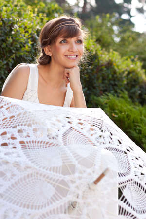 Portrait of beautiful greek smiling woman bride with decorative white umbrella against background green nature  Sunny outdoor Stock Photo - 15996806