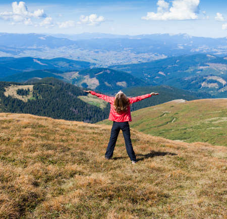 Young happy woman tourist standing on the mountain with raised hands embracing vitality freedom feeling success  Looking to a sky photo