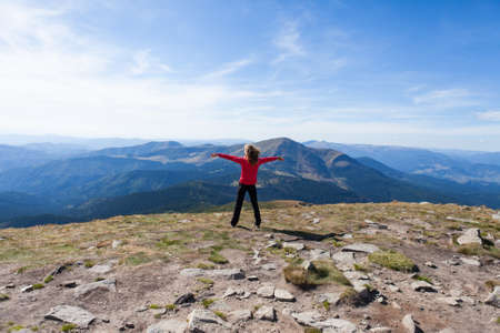 Hiker woman standing on mountain edge and looking to a sky with raised hands embracing vitality freedom  Position back to us Stock Photo