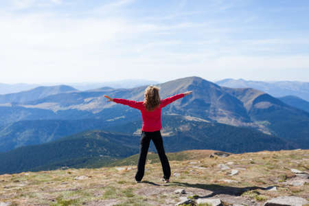 Happy hiker woman standing on a peak over the mountain with raised hands embracing vitality freedom feeling success and looking to a sky  Position back to us