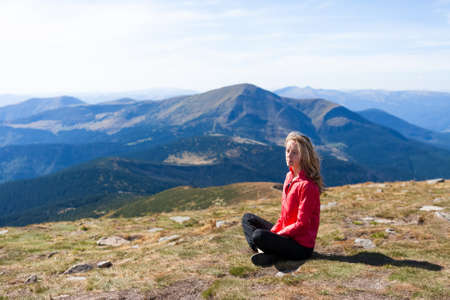 ecotourism: Young hiker woman sitting on a halt against the background of mountains