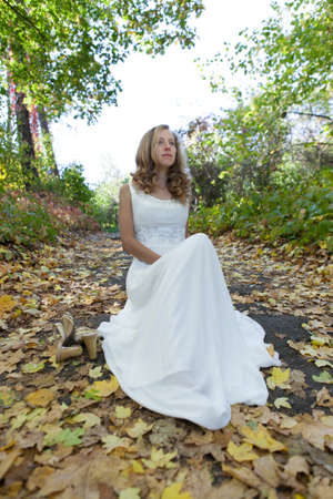 Young bride in white dress sitting on the footpath among fallen leaves in autumn nature photo