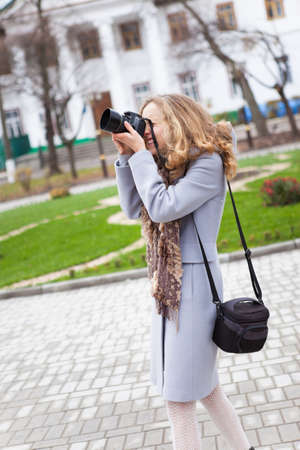 photojournalist: Woman press photographer shooting in city against the background green flowerbed and city building