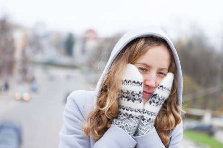 Frozen young woman heated by wool mittens and a from hood against the blurred background city  Outdoor