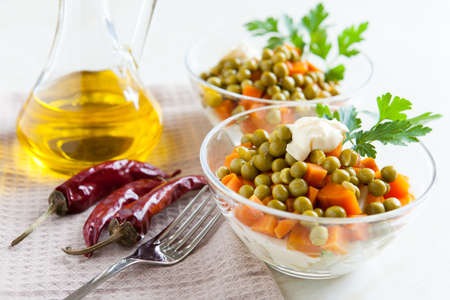 Vegetarian salad with canned peas and boiled vegetables  Hot peppers, bottle vegetable oil and fork on napkin fabric Stock Photo - 16665398