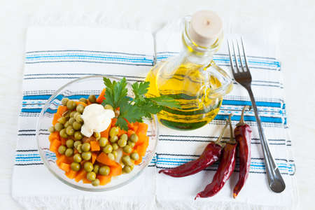 Vegetarian salad with canned peas and boiled carrots  Vegetable oil, hot peppers and fork  Top view Stock Photo - 16665396