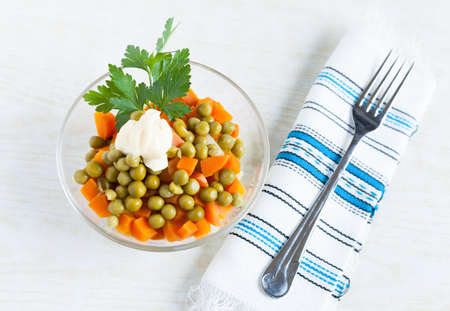 Vegetarian salad with canned green peas, boiled carrots, mayonnaise and fork  Top view Stock Photo - 16665384