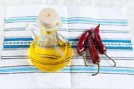 chiles picantes: Botella de aceite vegetal y tres pimientos picantes en vista artesanal alimentaria tela Top ingredientes
