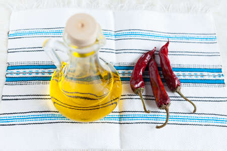 Bottle vegetable oil and three hot peppers on handmade fabric  Food ingredients  Top view Stock Photo - 16665400