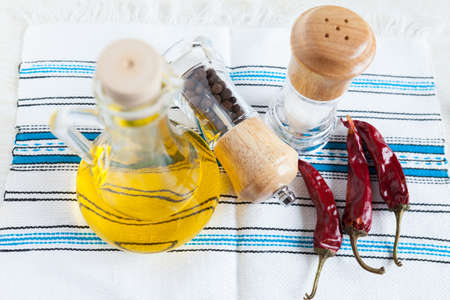 Bottle vegetable oil, spices and three hot peppers on handmade fabric  Food ingredients  Top view photo