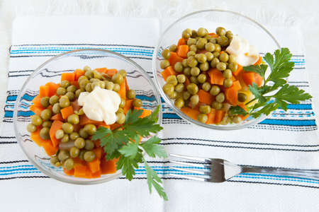 Salad with canned green peas, boiled carrots and mayonnaise on handmade fabric  Top view Stock Photo - 16665401