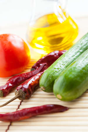 Red Chili Peppers, cucumber, tomato and bottle vegetable oil close-up  Food ingredients Stock Photo - 16665345