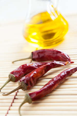 Red hot peppers and bottle vegetable oil on bamboo mat close-up Stock Photo - 16665358