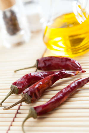 Red Chili Peppers and bottle vegetable oil on bamboo mat close-up  Food ingredients Stock Photo - 16665360
