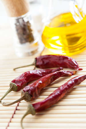 Red Chili Peppers, bottle vegetable oil and pepper-castor on bamboo mat close-up Stock Photo - 16665361