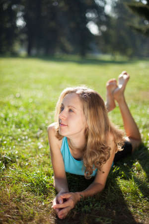 Young girl enjoying relaxation lying in the fresh green grass in the park illuminated by the rays of sunlight  Outdoor photo