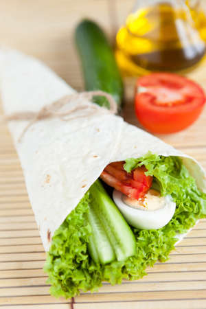 Fresh vegetables with egg in tortilla on bamboo mat  Healthy food Stock Photo