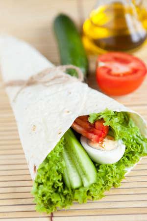 Fresh vegetables with egg in tortilla on bamboo mat  Healthy food Reklamní fotografie