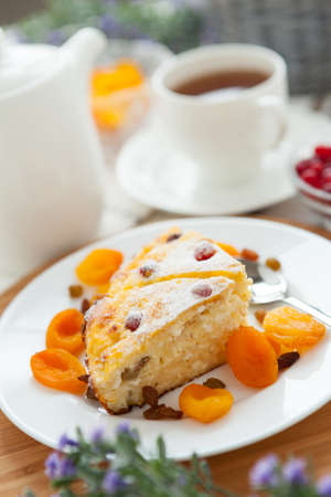 Cheese cake with tea, dried apricot and raisins closeup on a plate  Tasty dessert decorated