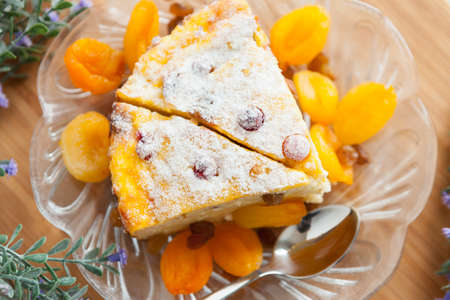 Cheese cake with dried apricot and raisins close-up on a plate  Tasty dessert photo