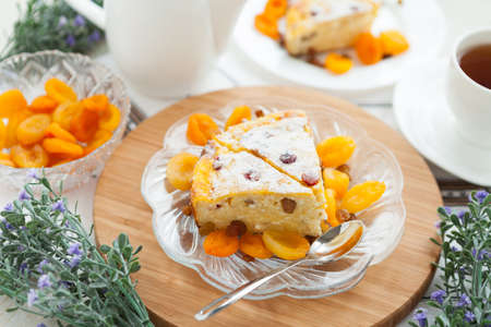 Cheese gratin closeup with dried apricot and raisins  Tasty dessert on a glass plate photo