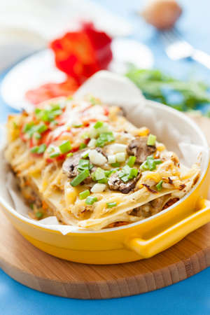 Delicious Italian Lasagna in yellow dish on a wooden kitchen board