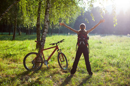 Excited girl cyclist standing in a spring park with hands outstretched. Sunny outdoor photo
