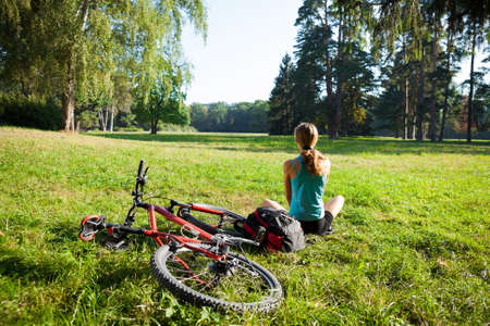 Girl cyclist with bike and backpack relax front view panorama of the sunny spring park Stock Photo