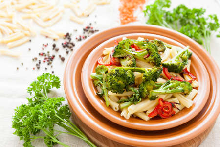 Delicious pasta with roasted vegetables on a plate closeup. Italian food photo