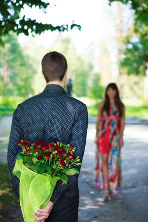 Romantic young man giving a bouquet of red roses to his girlfriend. Sunny park Stock Photo - 17501173