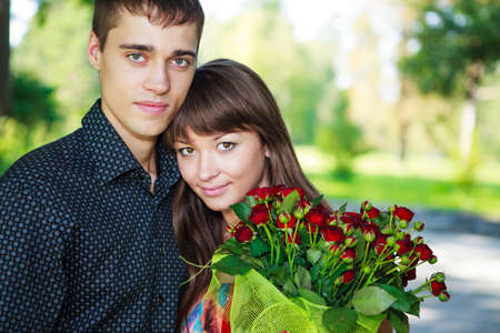 Portrait beautiful lovers young couple with a bouquet of red roses. Sunny summer outdoor photo