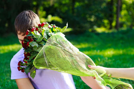 Young man gets hit in the face bouquet of red roses  The sunny nature of the background photo