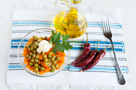 Salad with canned peas and carrots. Vegetable oil, hot peppers and fork. Top view Stock Photo - 17575013