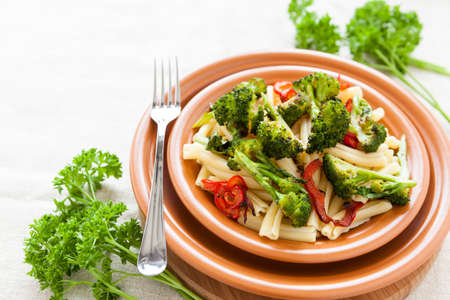 Pasta with pepper and broccoli on a plate closeup. Selective focus photo