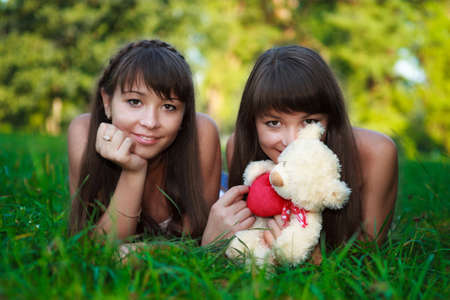 Portrait beautiful young twins sisters relaxation lying on the green grass in a sunny summer green park. Outdoor photo