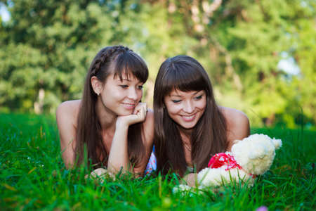 Beautiful young twins sisters with a soft toy relaxation lying on the green grass in a sunny summer green park  Outdoor photo