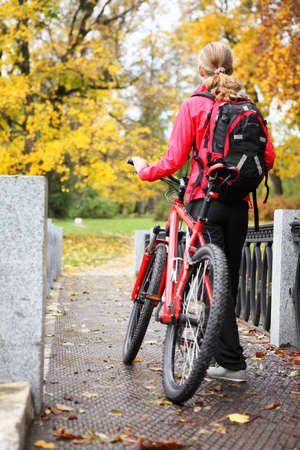 Woman cyclist with bike and backpack bicycle walk in autumn park photo
