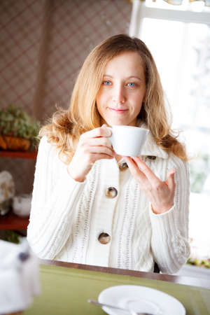 coffeebreak: Smiling young woman with a cup of coffee in hand  Coffee-break