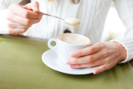 coffeetime: Closeup of cup coffee and woman hands. Girl on a coffee-break. Cup of hot beverage