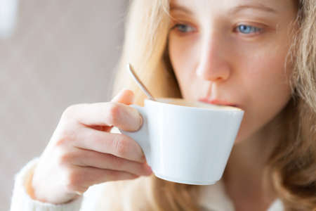 coffeetime: Young woman drinking coffee  Cup of hot beverage  Coffee-time