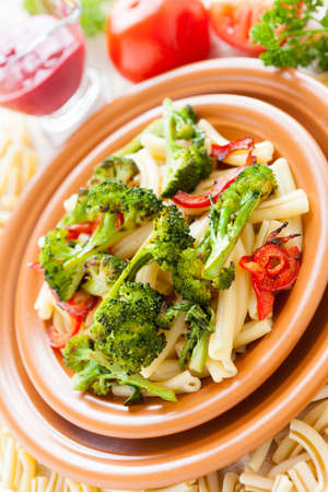 Nutritious pasta with pepper and broccoli closeup  Selective focus  Tasty italian food photo