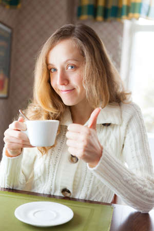 coffeebreak: Happy young woman with a cup of coffee in hand showing thumb up sign  Coffee-break Stock Photo