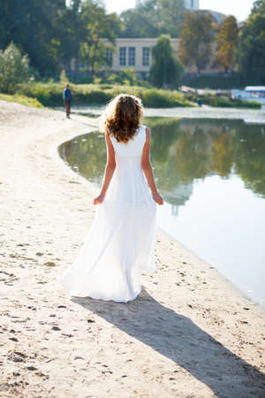 Young girl bride in a white dress walk the sunny coast of the river. Outdoor photo