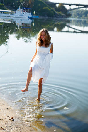 Young girl bride having fun on the splashing water in the river on the beach on a sunny morning. Outdoor photo