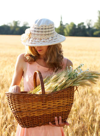 Beautiful woman in the hat with basket full of ripe ears wheat in the wheat field on a sunny day. Concept of abundance photo