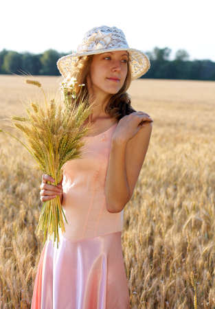 Beautiful woman in the hat holding wheat ears in her hand against a background of wheat field. Concept of abundance