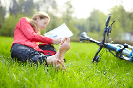 Girl cyclist on a halt reads lying in fresh green grass barefoot   Enjoying relaxation outdoors photo